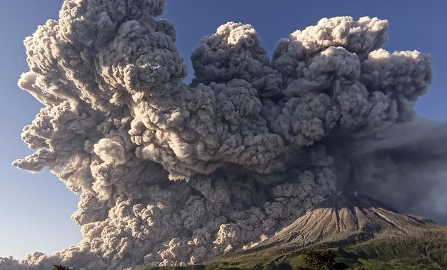 Mount Sinabung spews volcanic material during an eruption in Karo, North Sumatra, Indonesia, Tuesday, March 2, 2021. The 2,600-metre (8,530-feet) volcano erupted Tuesday, sending volcanic materials a few thousand meters into the sky and depositing ash on nearby villages. (Photo by Sastrawan Ginting/Antara Foto via Reuters)