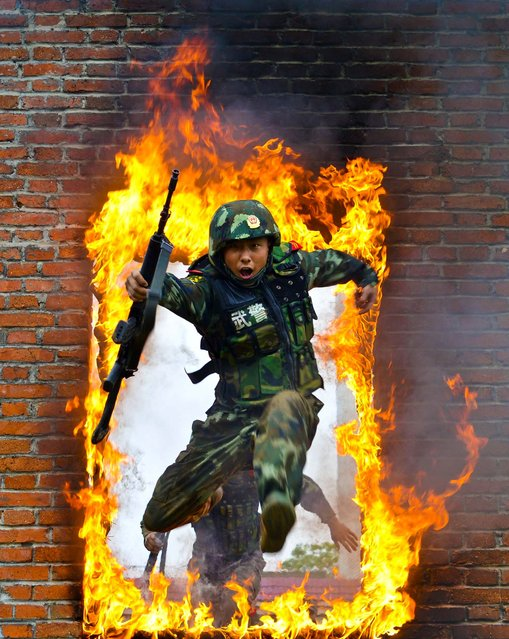 A paramilitary policeman jumps through a fire barrier during a military training exercise in Chuzhou, Anhui province, on July 23, 2013. (Photo by China Daily/Reuters)