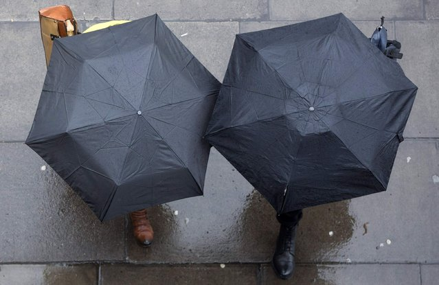 People shelter under umbrellas as they walk through central London January 31, 2015. (Photo by Neil Hall/Reuters)