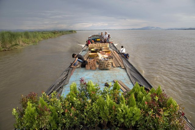 In this  June 29, 2016, photo, passengers travel in a ferry in Irrawaddy River, close to Bhamo, northern Kachin state in Myanmar. Much of the wood stripped from Sagaing town floated on the Irrawaddy River is transported to neighboring China and India. Myanmar is struggling to stop illegal logging that has erased one-quarter of the country's valuable forests in a generation. (Photo by Gemunu Amarasinghe/AP Photo)