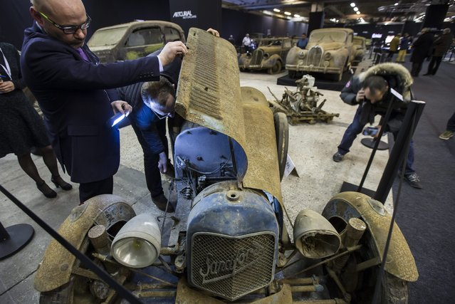 A prospective buyer inspects a Sandford Type S Cyclecar displayed as part of the Artcurial section of the Retromobile classic automobile show at the Parc des Expositions exhibition hall in Paris, France, 03 February 2015. (Photo by Ian Langsdon/EPA)