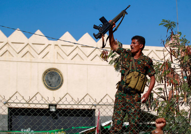 """A security member loyal to Yemen's Huthi movement lifts his firearm during a demonstration in front of the closed US Embassy in the capital Sanaa, on January 18, 2021, to reject the outgoing US administration's decision to designate the Huthis a """"foreign terrorist organisation"""". Impoverished Yemen is mired in a devastating conflict between Iran-backed Huthi rebels and government forces backed by Saudi Arabia that has left tens of thousands dead and sparked a dire humanitarian crisis. (Photo by Mohammed Huwais/AFP Photo)"""