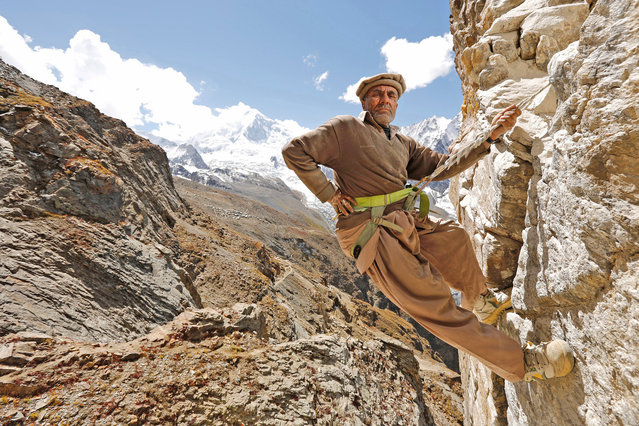 High in Northern Pakistan's Karakorum Range an illegal gem miner climbs up to his mine. These miners are amongst the highest in the world with this mine being located just short of 5,000 metres. (Photo by Hugh Brown/South West News Service)