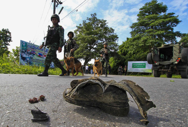 Thai security personnel inspect the site of a bomb attack on a roadside in Yala province, south of Bangkok, August 5, 2013. Five field army soldiers were injured after the explosion by suspected Muslim militants, as they were making their way to provide escort to teachers travelling to school, police said. (Photo by Surapan Boonthanom/Reuters)