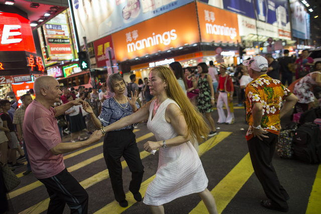 People dancing to buskers performances in Sai Yeung Choi Street South in Mongkok district, Hong Kong, China, 28 July 2018. (Photo by Jerome Favre/EPA/EFE)