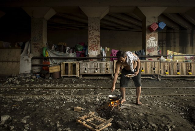 A man cooks dinner along a train track in Manila, Philippines on July 31, 2018. (Photo by Noel Celis/AFP Photo)