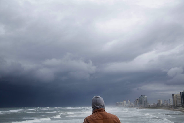 A man overlooks he high waves in the Mediterranean Sea in Tel Aviv, Israel, Wednesday, January 7, 2015 during a heavy winter storm sweeping through the Middle East.(Photo by Oded Balilty/AP Photo)