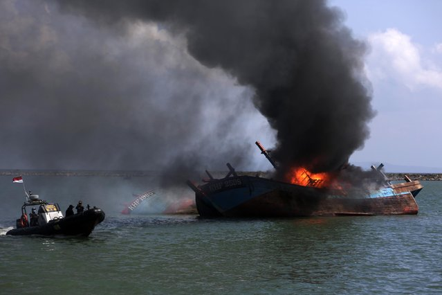 Smoke rises from a boat as the Ministry of Maritime Affairs and Fisheries destroyed two illegal fishing boats from Malaysia, off the coast of Banda Aceh, Indonesia 18 March 2021. Indonesia has destroyed illegal foreign fishing boats across the country as part of an ongoing push to stop illegal fishing in its waters. (Photo by Hotli Simanjuntak/EPA/EFE)