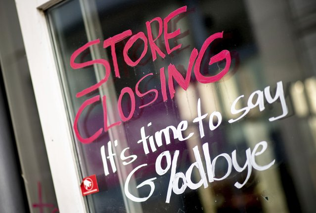 "The words ""Store Closing"" and the addition ""It's time to say Goodbye"" with a percent sign are written on the window of a closed store in the city center in Oldenburg, Germany, Thursday, April 1, 2021. In view of sharply rising Corona infection figures, the German government has extended the lockdown in Germany until April 18, 2021. (Photo by Hauke-Christian Dittrich/dpa via AP Photo)"