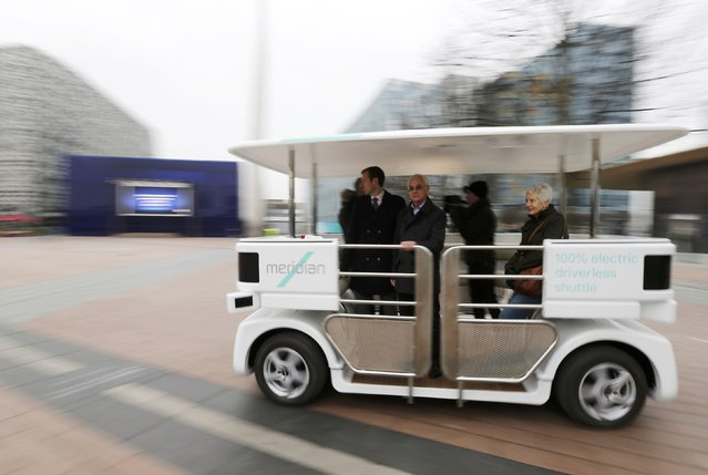 People ride a prototype of a driverless vehicle as it is moves through a pedestrian area in Greenwich, east London, February 11, 2015. (Photo by Suzanne Plunkett/Reuters)