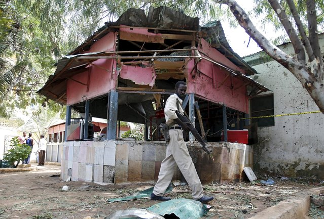 A Somali policeman walks near a small local restaurant attacked by a suicide bomber in Mogadishu January 2, 2016. (Photo by Feisal Omar/Reuters)
