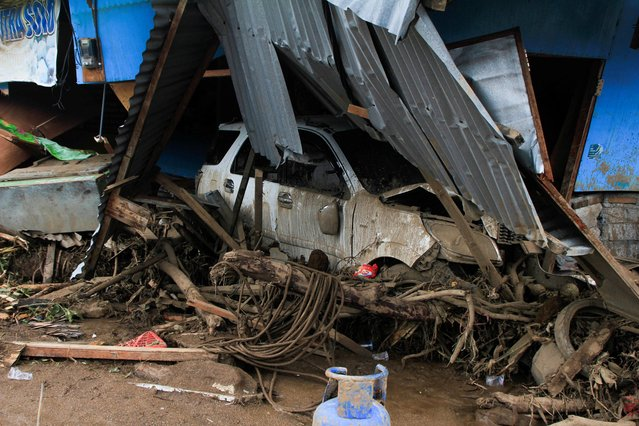 A damaged car is pictured following flash floods triggered by a tropical cyclone in East Flores, East Nusa Tenggara province, Indonesia, April 6, 2021. (Photo by Aditya Pradana Putra/Antara Foto via Reuters)