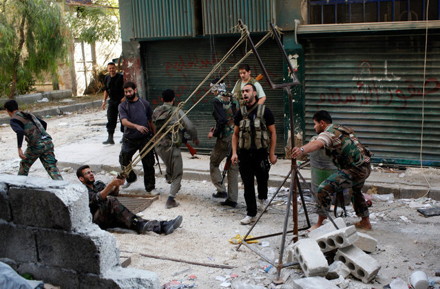 """Members of the """"Free Syrian Army"""" use a giant slingshot to launch a homemade bomb during clashes with pro-government soldiers in the city of Aleppo, October, 15, 2012. (Photo by Asmaa Waguih/Reuters)"""