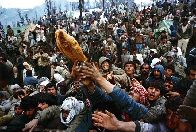 Frantic Kurdish refugees struggle for a loaf of bread during a humanitarian aid distribution at the Iraqi-Turkish border in this April 5, 1992 file photo. Yannis Behrakis: At the end of the first Iraq war about 1.5 million Kurds were fleeing in panic trying to escape from forces loyal to Saddam Hussein. (Photo by Yannis Behrakis/Reuters)