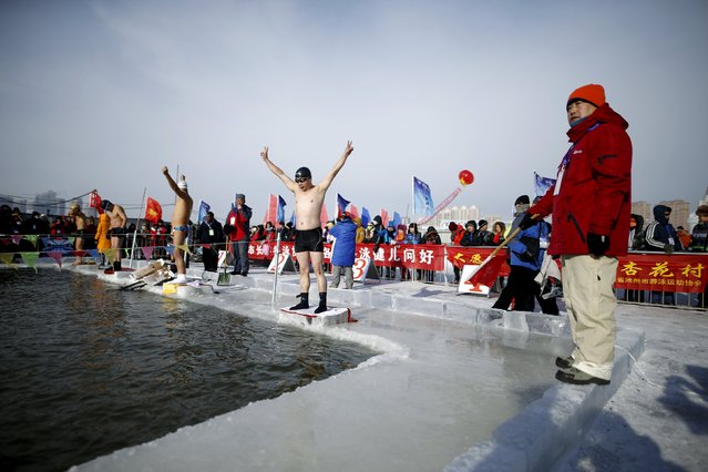 Swimmers wave in a pool carved from thick ice covering the Songhua River during the Harbin Ice Swimming Competition in the northern city of Harbin, Heilongjiang province, January 5, 2016. (Photo by Aly Song/Reuters)