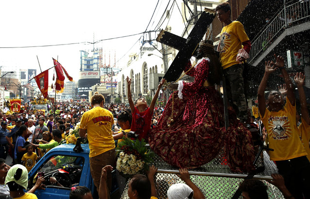 Devotees are sprinkled with holy water during a procession of Black Nazarene replicas two days before the annual procession of the Black Nazarene in Manila, Philippines January 7, 2016. (Photo by Erik De Castro/Reuters)