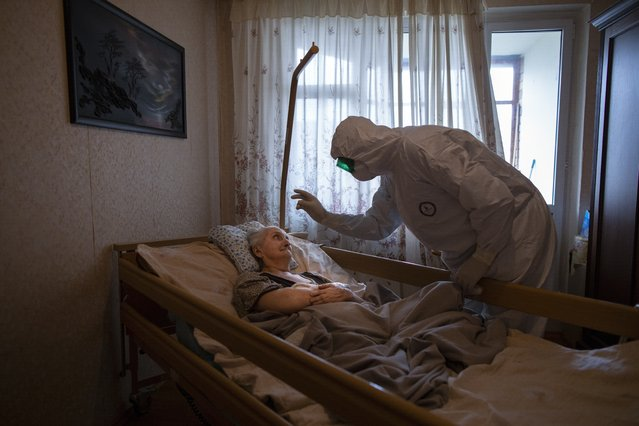 """Father Vasily Gelevan, a Russian Orthodox priest, blesses Lyudmila Polyak, 86, who is believed to be suffering from COVID-19, at her apartment in Moscow, June 1, 2020. Associated Press photographer Alexander Zemlianichenko says this of the image: """"I feel it's both very intimate and also deeply symbolic, an image of empathy and self-denial in the face of mortal danger"""". He says taking the photo was """"also very important for me on a personal level, an experience that transformed me, helping overcome my own fear"""" of the virus. (Photo by Alexander Zemlianichenko/AP Photo)"""