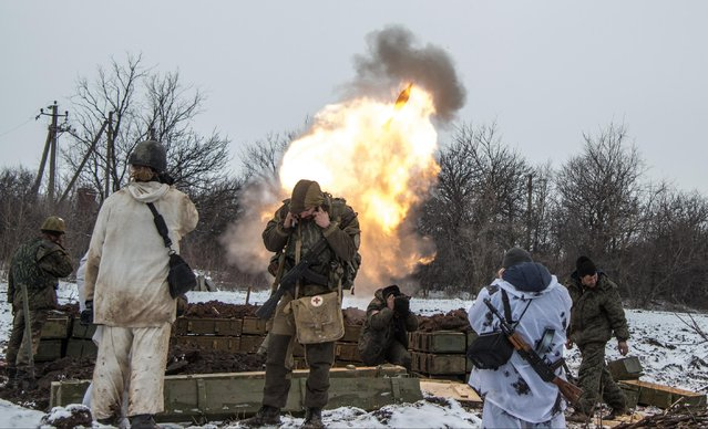 Russian-backed separatists cover their ears as they fire a mortar towards Ukrainian troops outside the village of Sanzharivka, northeast of Debaltseve, eastern Ukraine, Wednesday, February 11, 2015. (Photo by Maximilian Clarke/AP Photo)
