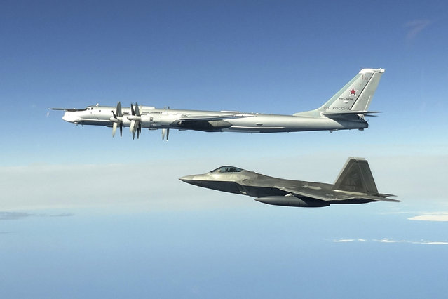 In this image taken Tuesday, June 16, 2020,  and released by the North American Aerospace Defense Command, a Russian Tu-95 bomber, top, is intercepted by a U.S. F-22 Raptor fighter off the coast of Alaska. Russian nuclear-capable strategic bombers have flown near Alaska on a mission demonstrating the military's long-range strike capability. The Russian Defense Ministry said that four Tu-95 bombers have flown over the Sea of Okhotsk, the Bering Sea, the Chukchi Sea and the Northern Pacific during an 11-hour mission. The ministry said the bombers were escorted by U.S. F-22 fighters during part of their patrol. (Photo by North American Aerospace Defense Command via AP Photo)