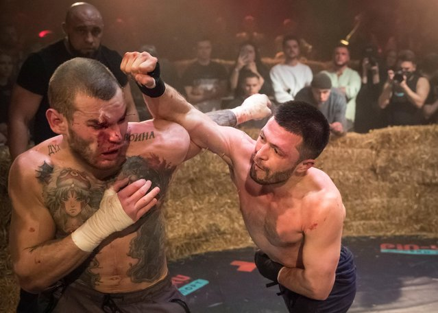 """Danik Vesnenok and Danila Utenkov fight during the """"Top Dog"""" bare-knuckle boxing tournament in Moscow, Russia on April 16, 2021. The tournament began broadcasting fights in parking lots in early 2020, but now rents out a Moscow sports arena for bare-knuckle bouts that are viewed online by millions. The most popular fight yet has been viewed over 13 million times on YouTube. The organizers attribute the sport's popularity to pent-up aggression because of COVID-19 restrictions and frustrations over the economy. (Photo by Shamil Zhumatov/Reuters)"""