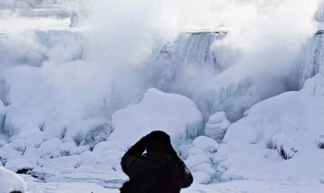 A man photographs ice masses formed around the American Falls as seen from Niagara Falls, Ontario, Canada, Thursday, February 19, 2015. (Photo by Aaron Lynett/AP Photo/The Canadian Press)