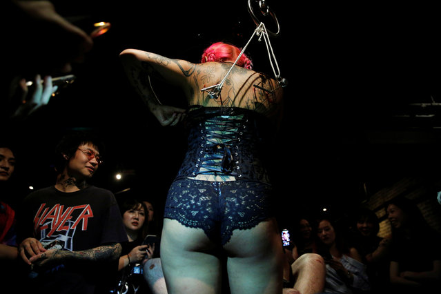 July waits to be suspended from hooks pierced through her skin by professional body artist Wei Yilaien at a bar in Shanghai, China on September 16, 2018. (Photo by Aly Song/Reuters)