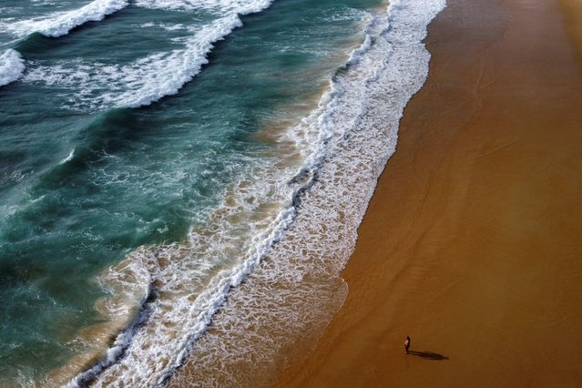 A man walks at the empty Karon beach on Phuket Island, Thailand on April 1, 2021. Picture taken with a drone. (Photo by Jorge Silva/Reuters)