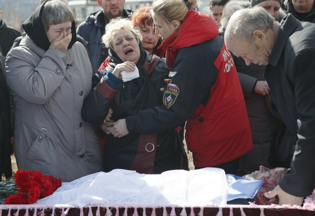 Relatives of a miner killed in an explosion on Wednesday at more than 1,000 meters (3,200 feet) underground at the Zasyadko mine, cry next to his coffin during a funeral for the victims of the accident in Donetsk, Ukraine, Friday, March 6, 2015. Tens of miners died in the accident. (AP Photo/Vadim Ghirda)