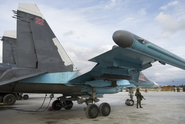 A Russian soldier stands guard next to a bomber at Hemeimeem air base in Syria on Wednesday January 20, 2016. (Photo by Vladimir Isachenkov/AP Photo)