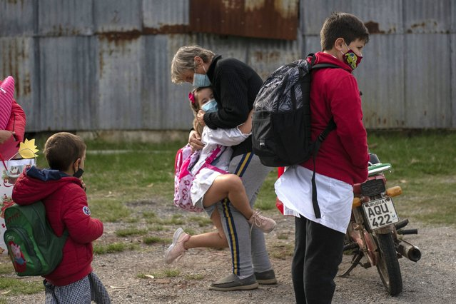 A student embraces a woman before entering school for the first time since it was closed due to the COVID-19 pandemic in Migues, Uruguay, Monday, May 3, 2021. Uruguay returned to face-to-face classes in some rural schools that have fewer than 20 students total and one teacher. (Photo by Matilde Campodonico/AP Photo)