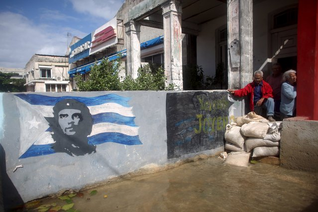 """Roberto Reyes and Zinaida Ayala stand next to sand bags protecting their home from flood water in Havana, January 23, 2016. An image of Cuba's revolutionary hero Ernesto """"Che"""" Guevara is pictured on the left. (Photo by Alexandre Meneghini/Reuters)"""