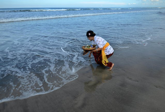 A Balinese woman places offerings in the sea during the Melasti ceremony prayer at Kuta beach on the island of Bali on March 18, 2015. (Photo by Sonny Tumbelaka/AFP Photo)