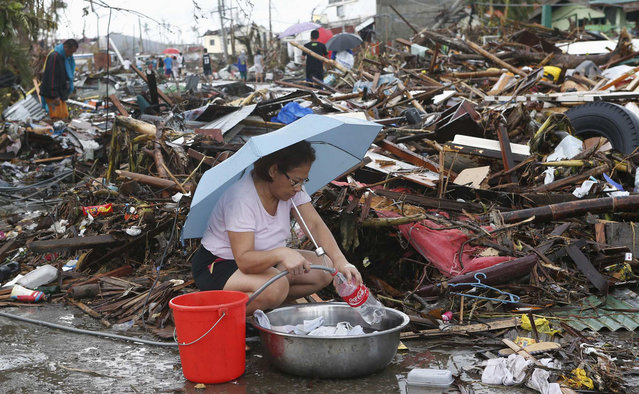 A resident gets water from a hose along a road blocked by debris, brought at the height of super typhoon Haiyan in Palo, Leyte province in central Philippines November 12, 2013. (Photo by Erik De Castro/Reuters)