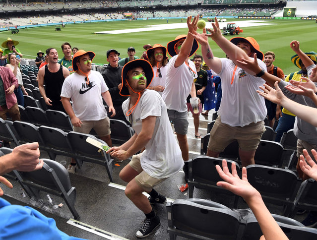 Spectators play an improvised game of cricket in the stands as rain forces Australia and Pakistan from the ground on the second day of the second cricket Test match in Melbourne on December 27, 2016. (Photo by William West/AFP Photo)