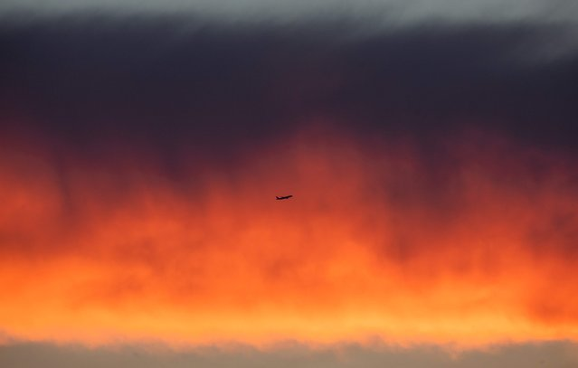 An airplane flies past a cloud band illuminated by the setting sun in Frankfurt am Main, western Germany, on August 09, 2018. (Photo by Frank Rumpenhorst/DPA via AFP Photo)