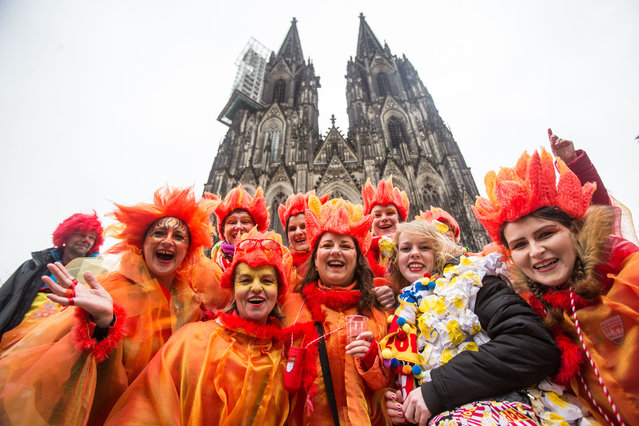 Carnival enthusiasts cheer and celebrate in front of the cathedral in Cologne, Germany, Thursday February 4, 2016. The street carnival has started in Cologne under increased security measures. After a string of robberies and sexual assaults on New Year's Eve in the city that police say were committed largely by foreigners, German authorities are keen to avoid a repeat of those events during the five-day street party. (Photo by Maja Hitij/DPA via AP Photo)