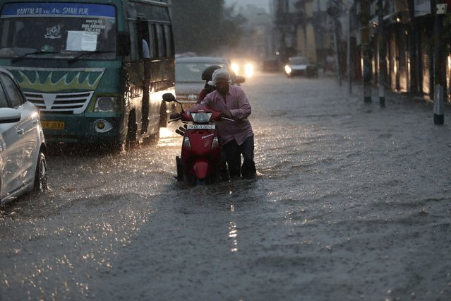 A man pushes a two wheeler through a flooded street during monsoon rains Jammu, India, Monday, July 12, 2021. (Photo by Channi Anand/AP Photo)