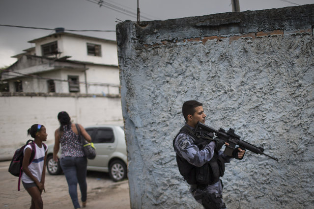 A military police officer patrols in the Roquette Pinto shantytown, part of the Mare slum complex in Rio de Janeiro, Brazil, Wednesday, April 1, 2015. The Brazilian army has begun to pull out of one of Rio de Janeiro's most violent slums, with police assuming responsibility for security in the area. (Photo by Felipe Dana/AP Photo)