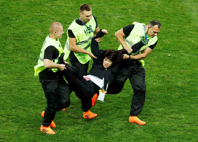 Stewards apprehend a pitch invader as France plays Croatia in the World Cup final in Moscow, Russia, July 15, 2018. (Photo by Maxim Shemetov/Reuters)