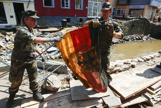 German Bundeswehr soldiers rescue a German national flag as they help to clean up following heavy rainfalls, in Bad Muenstereifel, North Rhine-Westphalia state, Germany, July 21, 2021. (Photo by Thilo Schmuelgen/Reuters)