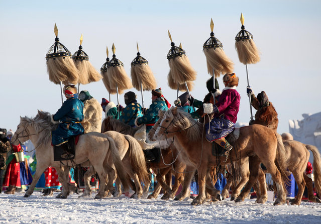 Participants in traditional Mongolian costumes ride horses at the opening ceremony of a winter Naadam fair in Hulunbuir, Inner Mongolia, China December 23, 2018. (Photo by Zhang Wei/CNS via Reuters)