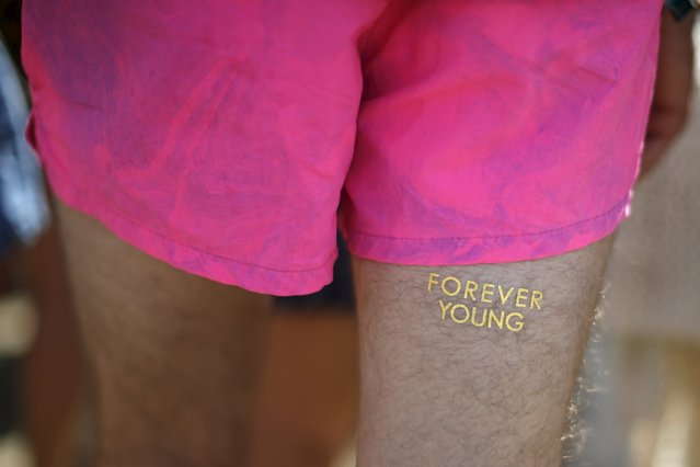 "A man displays a temporary tattoo saying ""Forever Young"" at the Coachella Valley Music and Arts Festival in Indio, California April 11, 2015. (Photo by Lucy Nicholson/Reuters)"