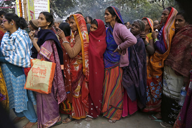 Pilgrims stand in queue to receive free evening meal at a transit camp on the way to Gangasagar, in Kolkata, India, Thursday, January 12, 2017. Thousands of Hindu pilgrims are expected to take the annual holy dip at Gangasagar, where the Ganges River reaches the Bay of Bengal, on the auspicious Makar Sankranti festival day that falls on Jan. 14. (Photo by Bikas Das/AP Photo)