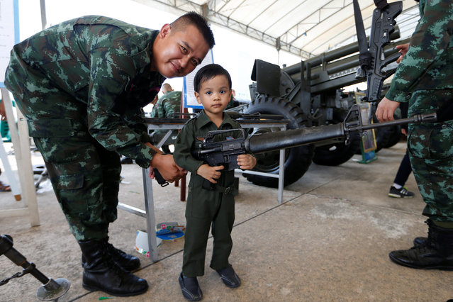 A boy and a Thai army soldier pose with a weapon during Children's Day celebration at a military facility in Bangkok, Thailand January 14, 2017. (Photo by Jorge Silva/Reuters)