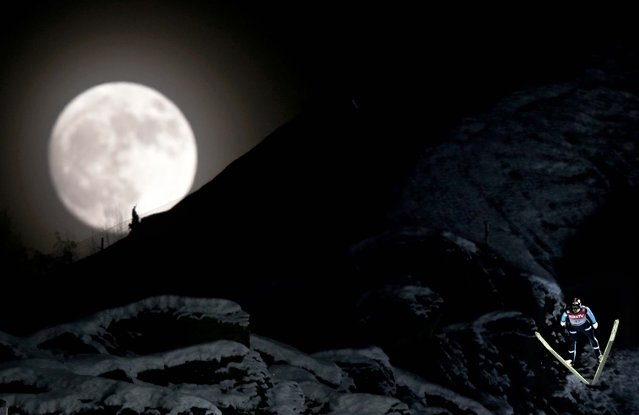Norway's Anders Bardal jumps during the official training session of the FIS Ski Flying World Cup in Vikersund, Norway on January 25, 2013, while a full moon rises over the mountain. (Photo by Daniel Sannum Lauten/AFP Photo)