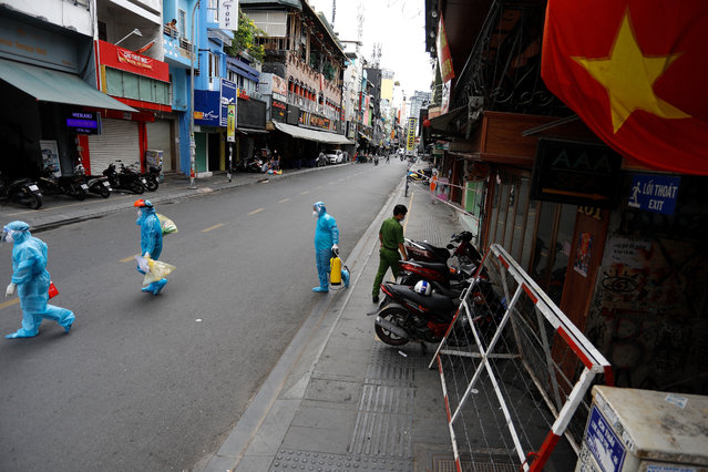 Medical workers collecting test samples from residents walk past in Ho Chi Minh City on July 9, 2021, on the first day of the government imposed two-week lockdown as a preventive measure to stop the spread of the COVID-19 coronavirus. (Photo by Huu Khoa/AFP Photo)