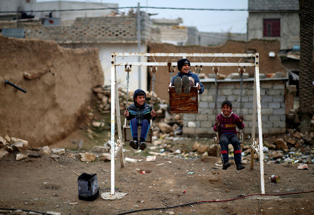 Iraqi children play on a crude swing along the frontline near Mosul at the Tigris river, Iraq, January 25, 2017. (Photo by Ahmed Jadallah/Reuters)