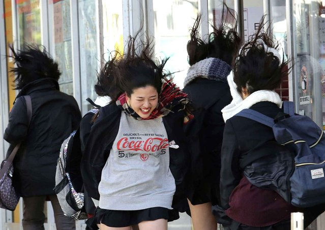 A girl smiles as her hair is blown by a strong wind in the Chinatown area in Yokohama, near Tokyo, Friday, January 27, 2017. (Photo by Koji Sasahara/AP Photo)