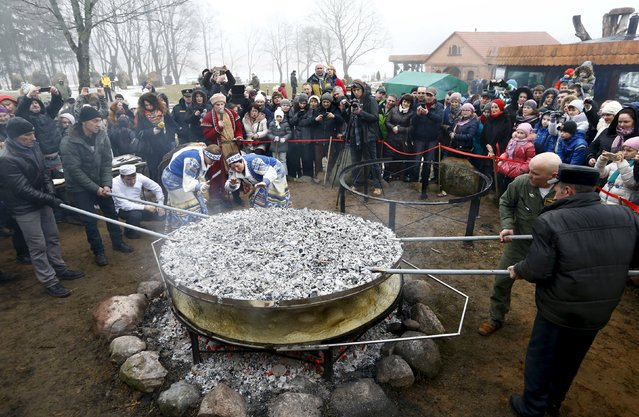 Employees prepare dranik, a potato pancake that is the national dish of Belarus, in the Sula History Park near the village of Sula, Belarus March 7, 2016. (Photo by Vasily Fedosenko/Reuters)