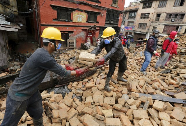 Volunteers build a chain to remove rubble with their bare hands from a house that was completely destroyed in Saturday's earthquake, in Kathmandu, Nepal, April 28, 2015. (Photo by Wolfgang Rattay/Reuters)